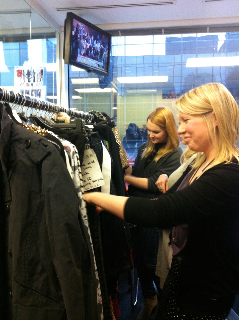Beth and Cyan searching through the clothing.